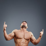 Πορτρέτο του ισχυρού μυϊκού ατόμου που δείχνει επάνω Στοκ φωτογραφία με δικαίωμα ελεύθερης χρήσης