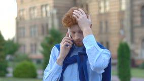 Πορτρέτο του καταθλιπτικού ατόμου με την κόκκινη τρίχα και της γενειάδας που μιλά μέσω του κινητού τηλεφώνου υπαίθριου απόθεμα βίντεο