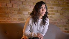 Πορτρέτο του καυκάσιου θρίλλερ προσοχής γυναικών brunette με τη διαταραχή στην άνετη εγχώρια ατμόσφαιρα φιλμ μικρού μήκους