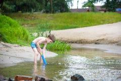 Πορτρέτο του καυκάσιου μικρού παιδιού στα παιχνίδια παιχνιδιού καπέλων αχύρου και της υδραντλίας στην παραλία Στοκ Φωτογραφίες