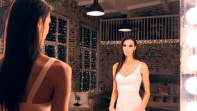 Πορτρέτο του κομψού κοριτσιού στην τοποθέτηση φορεμάτων βραδιού μπροστά από έναν καθρέφτη με τα φω'τα στο αποδυτήριο Brunette με απόθεμα βίντεο