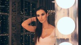 Πορτρέτο του κομψού κοριτσιού στην τοποθέτηση φορεμάτων βραδιού μπροστά από έναν καθρέφτη με τα φω'τα στο αποδυτήριο Brunette με φιλμ μικρού μήκους