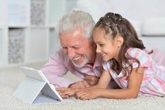 Πορτρέτο του κοριτσιού και του παππού με μια ταμπλέτα Στοκ φωτογραφία με δικαίωμα ελεύθερης χρήσης