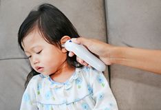 Πορτρέτο του κοριτσιού παιδιών με μια μέτρηση θερμομέτρων αυτιών Στοκ Εικόνα