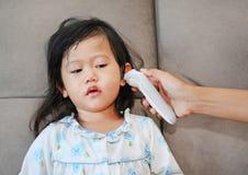 Πορτρέτο του κοριτσιού παιδιών με μια μέτρηση θερμομέτρων αυτιών Στοκ Εικόνες