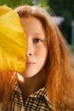 Πορτρέτο του κοριτσιού που καλύπτει το πρόσωπό της με το κίτρινο φύλλο Στοκ Φωτογραφία