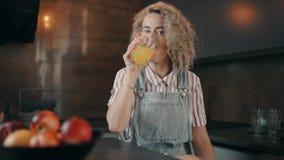 Πορτρέτο του κοριτσιού που πίνει το χυμό από πορτοκάλι και το χαμόγελο φιλμ μικρού μήκους