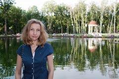 Πορτρέτο του κοριτσιού σε ένα υπόβαθρο της λίμνης στοκ εικόνα