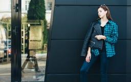 Πορτρέτο του κοριτσιού brunette που φορά το σακάκι δέρματος που στέκεται υπαίθρια στην πόλη ενάντια στο μαύρο αστικό τοίχο Στοκ εικόνα με δικαίωμα ελεύθερης χρήσης