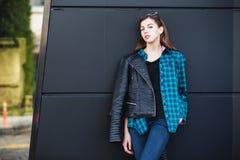 Πορτρέτο του κοριτσιού brunette που φορά το σακάκι δέρματος που στέκεται υπαίθρια στην πόλη ενάντια στο μαύρο αστικό τοίχο Στοκ εικόνες με δικαίωμα ελεύθερης χρήσης