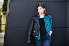 Πορτρέτο του κοριτσιού brunette που φορά το σακάκι δέρματος που στέκεται υπαίθρια στην πόλη ενάντια στο μαύρο αστικό τοίχο Στοκ φωτογραφία με δικαίωμα ελεύθερης χρήσης