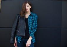 Πορτρέτο του κοριτσιού brunette που φορά το σακάκι δέρματος που στέκεται υπαίθρια στην πόλη ενάντια στο μαύρο αστικό τοίχο Στοκ Φωτογραφίες