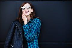 Πορτρέτο του κοριτσιού brunette που φορά το σακάκι δέρματος που στέκεται υπαίθρια στην πόλη ενάντια στο μαύρο αστικό τοίχο Στοκ Φωτογραφία