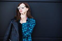 Πορτρέτο του κοριτσιού brunette που φορά το σακάκι δέρματος που στέκεται υπαίθρια στην πόλη ενάντια στο μαύρο αστικό τοίχο Στοκ Εικόνες