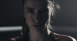 Πορτρέτο του κουρασμένου θηλυκού μπόξερ που στέκεται στο εγκιβωτίζοντας δαχτυλίδι και που εξετάζει τη κάμερα φιλμ μικρού μήκους