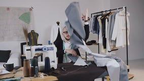 Πορτρέτο του κουρασμένων ράφτη και του σχεδιαστή μόδας με το ύφασμα στα χέρια του στο εργαστήριο Εξαντλημένη μοδίστρα Τρελλός και φιλμ μικρού μήκους