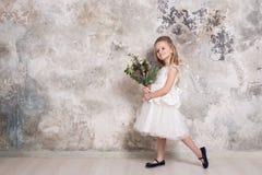 Πορτρέτο του λίγο ελκυστικού κοριτσιού σε ένα άσπρο φόρεμα με μια ανθοδέσμη στα χέρια της στα πλαίσια ενός τοίχου grunge στοκ φωτογραφία