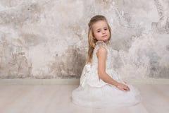Πορτρέτο του λίγο ελκυστικού χαμογελώντας κοριτσιού σε ένα άσπρο φόρεμα με την κατσαρωμένη τρίχα στα πλαίσια ενός τοίχου grunge στοκ φωτογραφίες