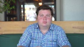 Πορτρέτο του λευκού καυκάσιου πεινασμένου λυπημένου μεγάλου παχιού ατόμου δυνατής μπύρας που φαίνεται άμεσα κεκλεισμένων των θυρώ απόθεμα βίντεο