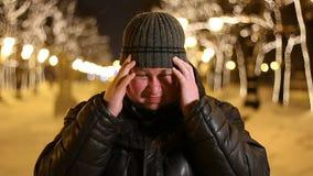 Πορτρέτο του λυπημένου ατόμου με τον πονοκέφαλο υπαίθρια κατά τη διάρκεια του κρύου χειμερινού βραδιού φιλμ μικρού μήκους