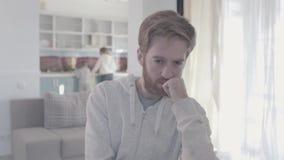 Πορτρέτο του λυπημένου γενειοφόρου ατόμου που στέκεται στο καθιστικό κοντά επάνω Η γυναίκα και το αγόρι είναι στο υπόβαθρο Οικογε απόθεμα βίντεο