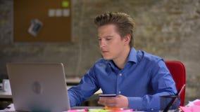 Πορτρέτο του μέσης ηλικίας ξανθού επιχειρηματία που πληρώνουν για το smth που χρησιμοποιεί την πιστωτική κάρτα και του lap-top στ απόθεμα βίντεο