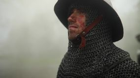Πορτρέτο του μεσαιωνικού ιππότη στο τεθωρακισμένο στο misty δάσος στη βροχή απόθεμα βίντεο