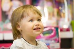 Πορτρέτο του μικρού κοριτσιού μεταξύ των παιχνιδιών στο κατάστημα παιδιών Στοκ φωτογραφία με δικαίωμα ελεύθερης χρήσης