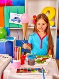Πορτρέτο του μικρού κοριτσιού με τη ζωγραφική βουρτσών στον παιδικό σταθμό Στοκ Φωτογραφία