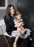 Πορτρέτο του μικρού κοριτσιού με τη μητέρα στον πίνακα, που κάνει τα μαθήματα Στοκ Εικόνα