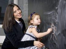 Πορτρέτο του μικρού κοριτσιού με τη μητέρα στον πίνακα, που κάνει τα μαθήματα Στοκ φωτογραφία με δικαίωμα ελεύθερης χρήσης