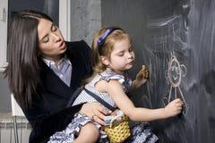 Πορτρέτο του μικρού κοριτσιού με τη μητέρα στον πίνακα, που κάνει τα μαθήματα Στοκ εικόνες με δικαίωμα ελεύθερης χρήσης
