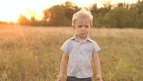 Πορτρέτο του μικρού παιδιού σε έναν τομέα στο ηλιοβασίλεμα φιλμ μικρού μήκους