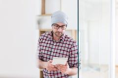 Πορτρέτο του μοντέρνου αρχιτέκτονα ή του σχεδιαστή με τη συσκευή ταμπλετών που στέκεται στο γραφείο στοκ εικόνα με δικαίωμα ελεύθερης χρήσης