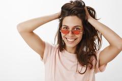 Πορτρέτο του μοντέρνου εύθυμου κοριτσιού κομμάτων στα κόκκινα γυαλιά ηλίου που αγγίζουν και που παίζουν με την όμορφη φυσική τρίχ στοκ εικόνες