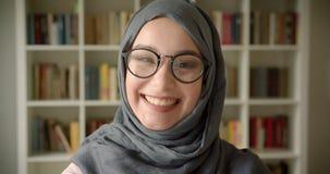 Πορτρέτο του μουσουλμανικού σπουδαστή στο hijab και το γέλιο γυαλιών που είναι χαρούμενα και συγκινημένα στη κάμερα στη βιβλιοθήκ απόθεμα βίντεο