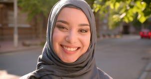 Πορτρέτο του μουσουλμανικού σπουδαστή στο hijab που χαμογελά και που ακτινοβολεί στη κάμερα που στέκεται στην πράσινη οδό πόλεων απόθεμα βίντεο