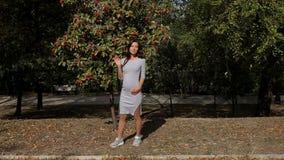 Πορτρέτο του νέου έγκυου κοριτσιού στο γκρίζο φόρεμα στο θερινό πάρκο φιλμ μικρού μήκους