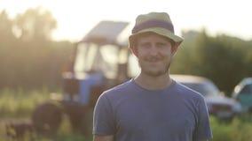Πορτρέτο του νέου αγρότη στο καπέλο που στέκεται στον τομέα του οργανικού αγροκτήματος και του χαμόγελου φιλμ μικρού μήκους