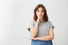 Πορτρέτο του νέου αρκετά όμορφου κοριτσιού που εξετάζει την τοποθέτηση καμερών με το χέρι στο πηγούνι πέρα από το άσπρο υπόβαθρο Στοκ Φωτογραφία