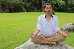 Πορτρέτο του νέου ασιατικού ατόμου που κάνει την περισυλλογή γιόγκας καθμένος στη θέση λωτού στο βράχο στο όμορφο υπαίθριο πάρκο στοκ εικόνες
