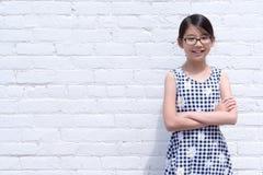 Πορτρέτο του νέου ασιατικού κοριτσιού ενάντια στον άσπρο τουβλότοιχο στοκ εικόνες