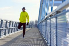 Πορτρέτο του νέου ατόμου αθλητών στο windbreaker που προετοιμάζεται να ασκήσει τους μυς τεντώματος στοκ φωτογραφία με δικαίωμα ελεύθερης χρήσης
