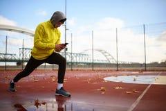 Πορτρέτο του νέου ατόμου αθλητών στο windbreaker που προετοιμάζεται να ασκήσει τους μυς τεντώματος στοκ φωτογραφίες με δικαίωμα ελεύθερης χρήσης