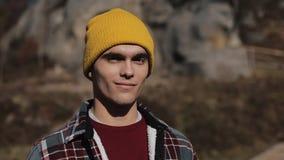 Πορτρέτο του νέου ατόμου οδοιπόρων που στέκεται στα βουνά και που χαμογελά στη κάμερα Όμορφο υπόβαθρο βράχων υπαίθρια φιλμ μικρού μήκους