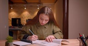Πορτρέτο του νέου βιβλίου ανάγνωσης έφηβη που γράφει προσεκτικά την εργασία στο copybook στην αρχή απόθεμα βίντεο