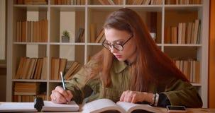 Πορτρέτο του νέου βιβλίου ανάγνωσης γυναικών σπουδαστών και της εργασίας γραψίματος στα ρολόγια copybook στη κάμερα στη βιβλιοθήκ απόθεμα βίντεο