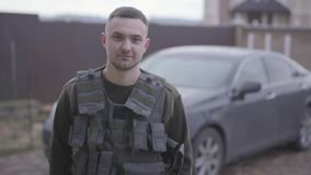 Πορτρέτο του νέου γενναίου στρατιωτικού που μένει και που χαμογελά στην οδό σε ομοιόμορφο στο υπόβαθρο του αυτοκινήτου φιλμ μικρού μήκους