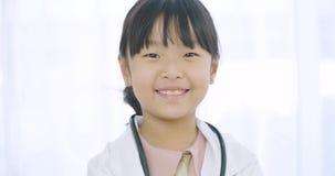 Πορτρέτο του νέου γιατρού μικρών κοριτσιών στο άσπρο παλτό με το στηθοσκόπιο που εξετάζει τη κάμερα φιλμ μικρού μήκους