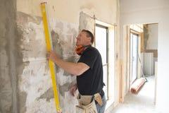 Πορτρέτο του νέου ελκυστικού ατόμου οικοδόμων που απασχολείται στη βέβαια μέτρηση και που ισοπεδώνει τον τοίχο με την οικοδόμηση  στοκ φωτογραφίες